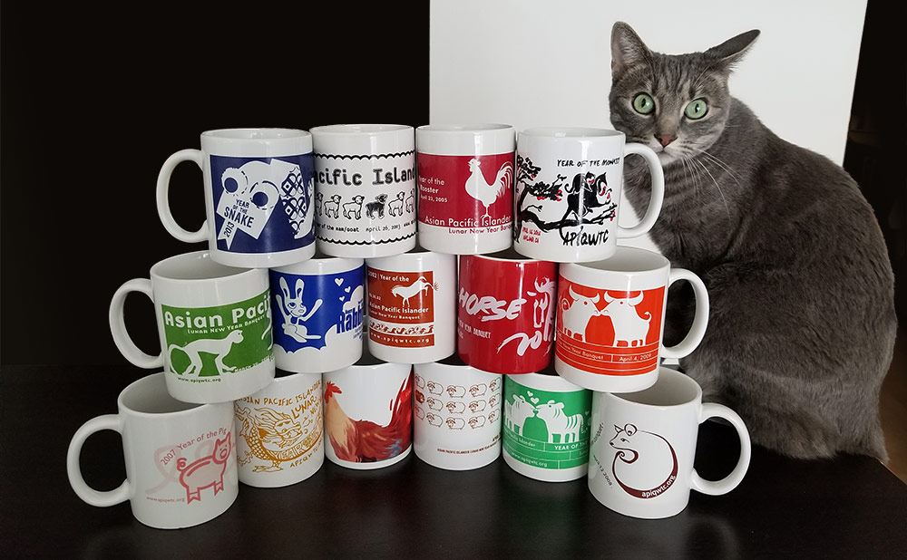 A gray cat sits next to 15 mugs from previous banquets stacked on top of one another.